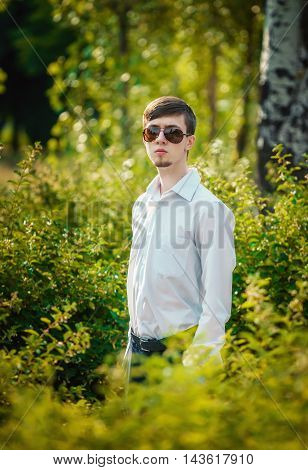 Handsome stylish young man with beard in sunglasses and white shirt with long sleeves standing in the park among green bushes