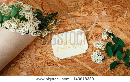 Birthday Card with Bouquet from White Flowers and Green Leaves.Craft Brown Paper on the Texture Wooden Background.Celebrations Wishes,Happy Birthday