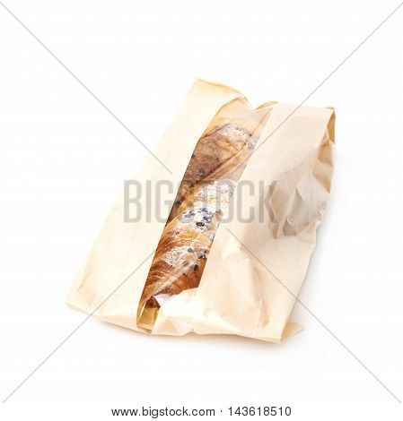 Fresh croissant in a paper bag isolated over the white background