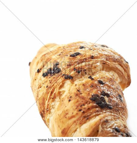 Chocolate croissant pastry isolated over the white background, close-up crop fragment with a shallow depth of field as a copyspace backdrop composition