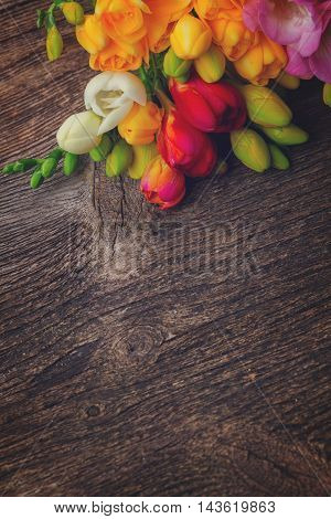 Fresh freesia flowers on wooden table with copy space, retro toned