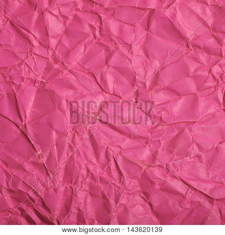Close-up fragment of a pink magenta crumpled paper texture as a backdrop composition
