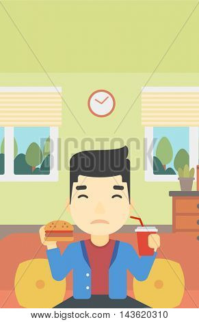 An asian young man sitting on a sofa while eating hamburger and drinking soda on the background of living room. Vector flat design illustration. Vertical layout.