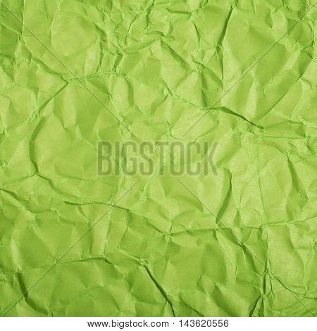 Close-up fragment of a green crumpled paper texture as a backdrop composition