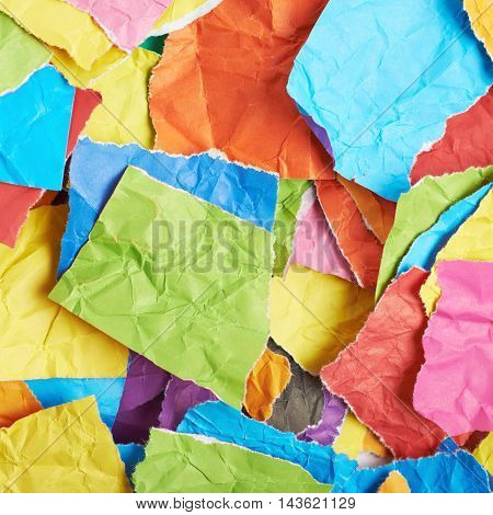 Surface covered with multiple colorful pieces of torn paper as an abstract background composition