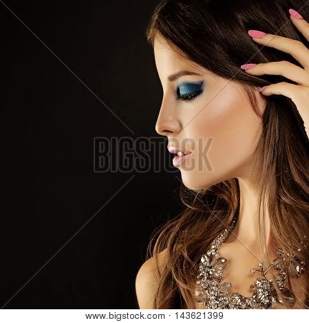 Beautiful Woman. Fashion Makeup and Jewelry on Dark Background