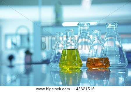 flask glassware with orange and yellow solution in blue science laboratory