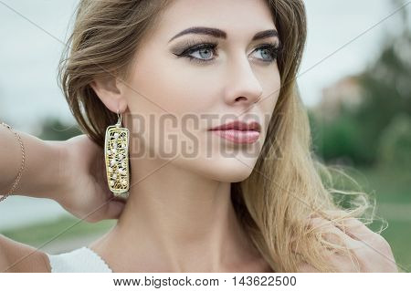 Close-up portrait of pretty young blond longhair woman with jewerly outdoors.