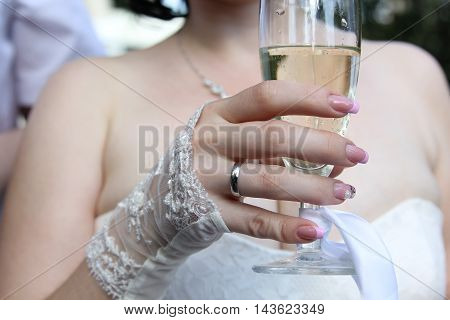 The bride at a wedding holding a glass of champagne