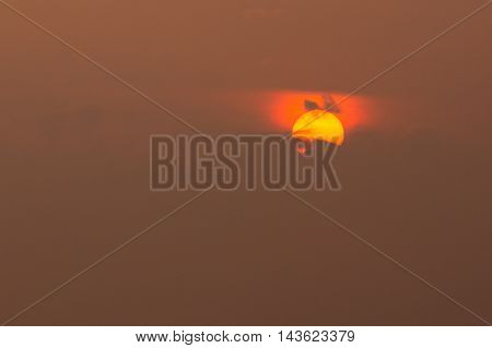 Close View Of Yellow Disk Of Setting Rising Sun With Red Glow Around, Partly Covered By Dark Clouds In Center, Brown Sky Background, Sunrise, Sunset, Dawn.
