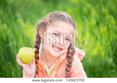 Sweet girl with a fallen toth holding an apple in her hand on nature
