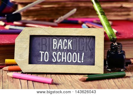 label-shaped chalkboard with the text back to school, some old books and old stationery such as a pen nib or some pencil crayons of different colors, on a rustic wooden table