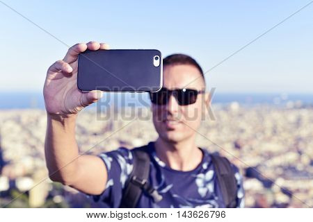 closeup of a young caucasian man taking a self-portrait with his smartphone in Barcelona, Spain, with a panoramic view of the city in the background