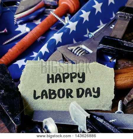 closeup of a piece of sandpaper with the text happy labor day written in it, a pile of different tools and a flag of the United States in the background