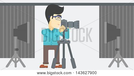 An asian young photographer working with camera on a tripod in photo studio. Man taking photo with professional digital camera in the studio. Vector flat design illustration. Horizontal layout.