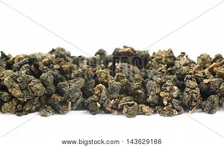 Line of dried green tea leaves isolated over the white background
