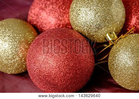 Selection of gold and red glitter Christmas tree decoration baubles on red cloth background