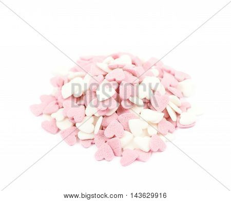 Pile of sugar pink heart shaped sprinkles isolated over the white background