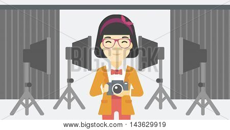 An asian young photographer holding a camera in photo studio. Photographer using camera in the studio. Woman taking photo with digital camera. Vector flat design illustration. Horizontal layout.