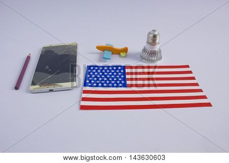 Modern mobile phone with broken screen on white background. led lamp US flag and a plane.