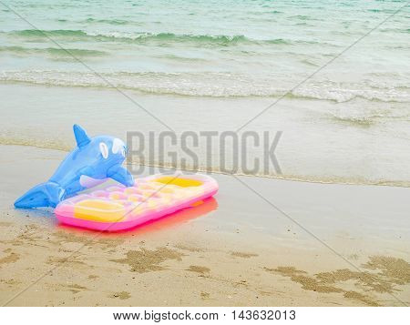 Inflatable dolphin and inflatable bed on the beach