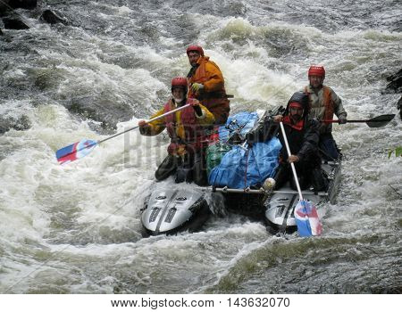 KOLA PENINSULA RUSSIA - 15 AUGUST 2008: Team of men on an inflatable catamaran at rough river