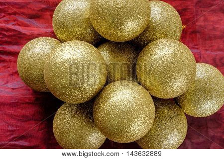 Top down image of pile of bright shiny gold glitter baubles for Christmas tree decorating on top of red cloth