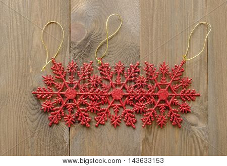 Group of three sparkly red glitter snowflake Christmas tree decorations lay flat on wooden background