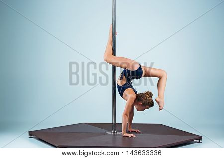 The strong and graceful sports young girl performing acrobatic exercises on pylon on blue background