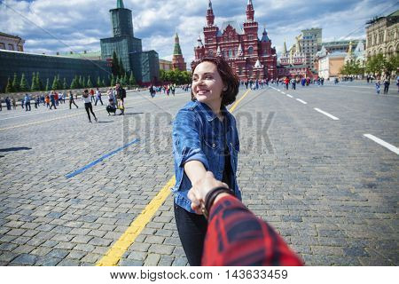 Follow Me. Young happy woman pulls the guys hand on the Red Square, Russian Moscow