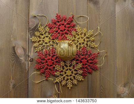 Group of sparkly Christmas tree decorations lay flat on wooden background. Red and gold glitter snowflakes in circle with one gold bauble in center
