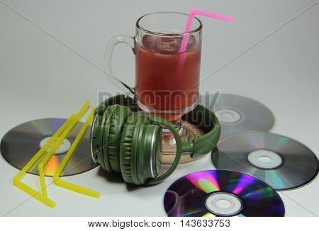 big green earphones on a table with disks and lemonade