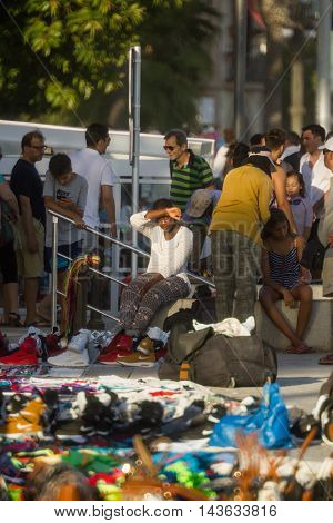 Sitges Spain - 21 August 2016: Tourists walking pass vendors that sell fake hi-end fashion brand name bags purses and sneakers in Sitges Spain on August 21 2016.
