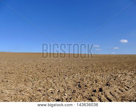 Cultivated Ploughed Field Under Blue Sky And Some Clouds