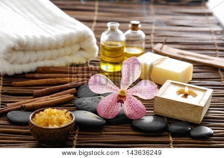 Spa setting with stones ,candle, oil ,soap on mat