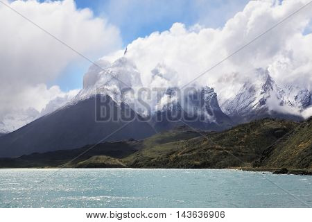 Magic beauty of Lake Pehoe. A strong wind blows turquoise waves on the lake, grand cliffs of Los Kuernos covered with snow and ice