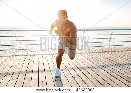 Focused african american young sportsman is ready to start running on pier