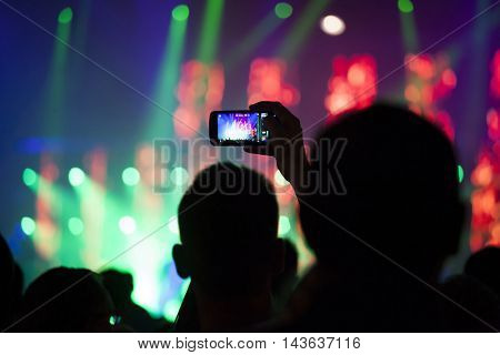 Taking photos with smart phone at festival, concert,