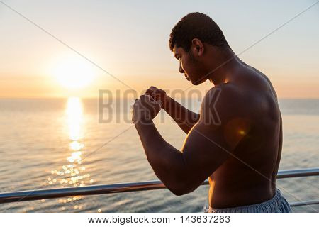 Silhouette of african american young man athlete doing boxing training in the morning