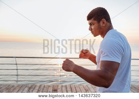 Athletic african american young sportsman working out in the morning