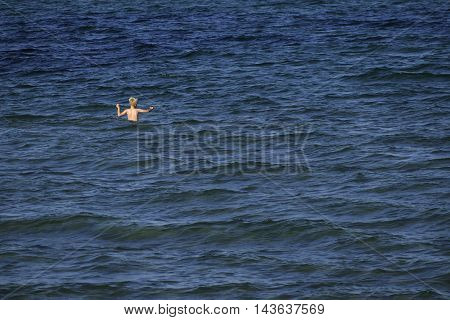 little boy child bathes in big blue sea generous copy space concept of vacation danger and learn to swim