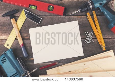 woodworking project tools and blank sheet on wooden table