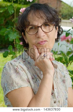 a middle aged woman with glasses in the garden