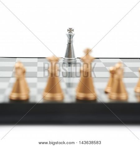 Chess board with the single silver king against full set of golden figures, close-up crop composition isolated over the white background