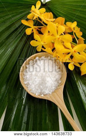 Spa set with yellow orchid and salt in bowl on palm leaf