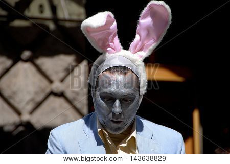 New York City - April 11 2009: Man with painted silver face wearing a bunny ears hat at the annual Easter Parade on Fifth Avenue