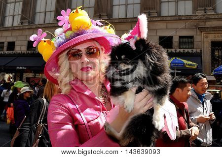 New York City - April 20 2014: Elegantl woman in a chic pink outfit holding her dog at the Easter Parade on Fifth Avenue