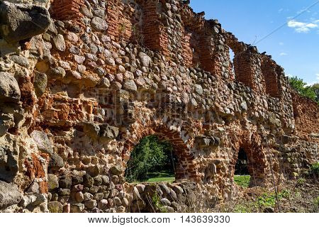 Red brick wall with arched doors and windows in ruins