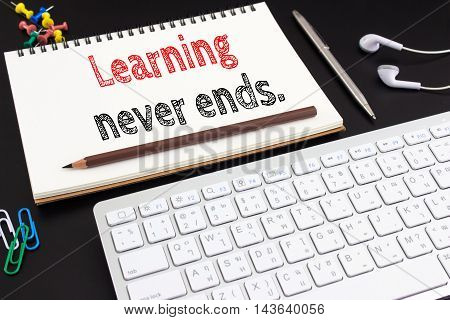 Word text Learning never end on white paper on office table / business concept