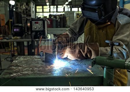 The man worker welding with sparks in factory